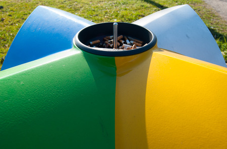 Ashtray and recycling bin in different colors in a playground