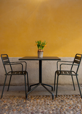 Two chairs and a table with daffosils on it outside an Italian restaurant - center of Milan