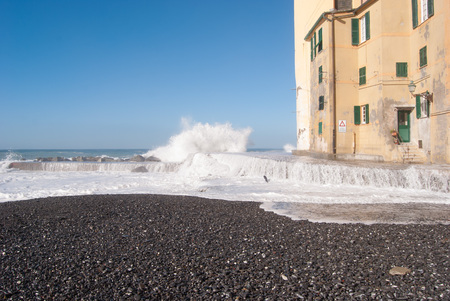 View of pier under a big wave and church wall of Camogli