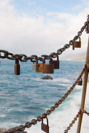Padlocks tied to a chain as a promise of love with sea as background