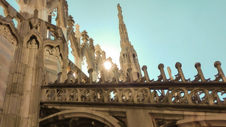 Some spiers of the Milan Cathedral with sun and a  blue sky