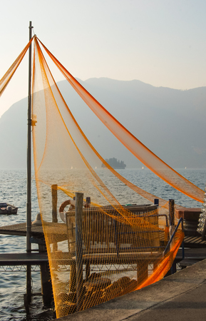 Fishing nets attached to a pole with panorama of the Iseo lake