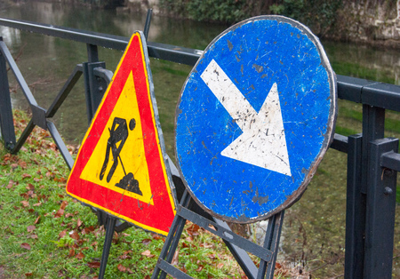 Worn road signs in the shape of circle and triangle indicating work in progress