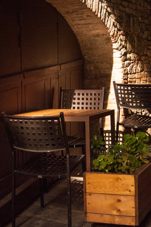 Two chairs and a table with geranium on it outside an Italian restaurant