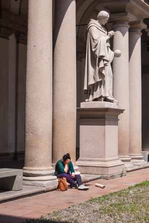 Girl sitting near the marble statue of the statue of the Italian mathematician inventor of the axonometric cavalier
