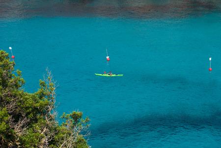 Boy paddling on a canoe in the crystalline sea of Menorca Reklamní fotografie