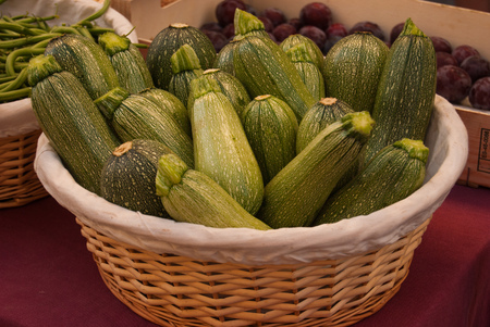 Wicker basket with ripe zucchini at a local weekly market