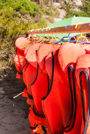 Many life jackets hanging on the beach Imagens