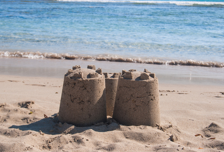 Castle of sand with three towers by the sea 스톡 콘텐츠