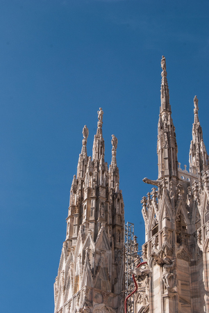 Many lateral spiers surmounted by statues of the Milan Cathedral with a clear and blue sky