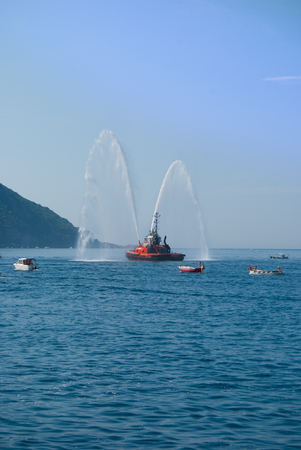 Naval vessel of firefighters with high splashes of sea water