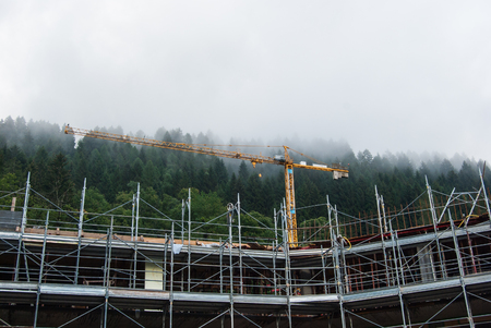 Metal scaffolding and yellow cranes with low clouds above the Abies of a forest