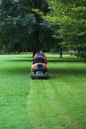 Man at work while sitting on a lawnmower Foto de archivo