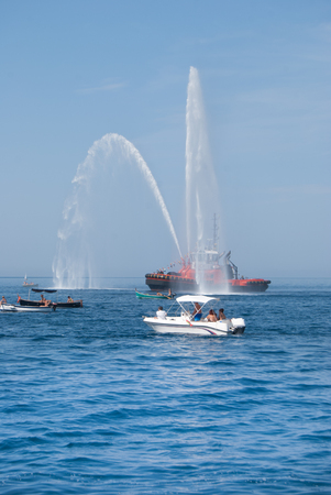 Two jets of sea water sprayed by a fire engine of a firefighters red boat