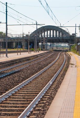 Train tracks and platform at a little station with traffic light and bridge in cement Archivio Fotografico