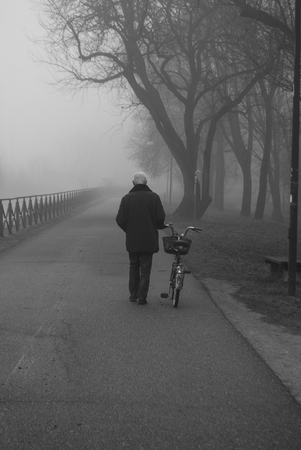 Man walking while he pulls his bike during a foggy day Stock Photo