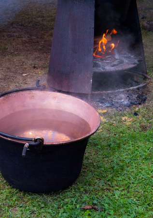 Copper cauldron close to flame point an old method of cooking polenta