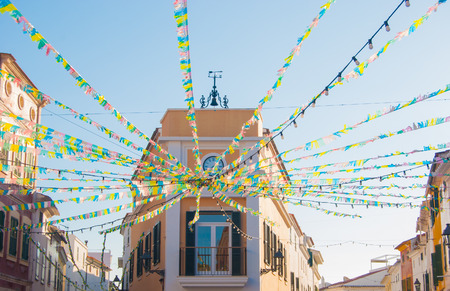 A lot of little and colorful flags arranged in a radial pattern of a little town of Menorca