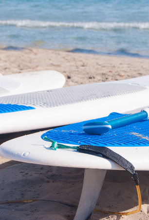Three surfboards white and blue laid on the beach