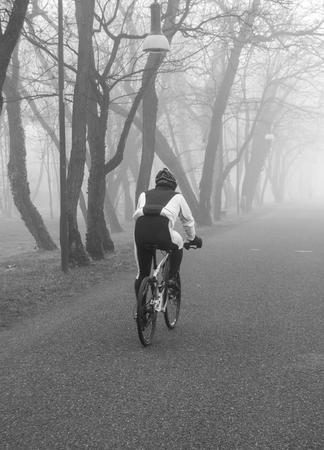 A man on cycle in the middle of a fog Reklamní fotografie - 111284906