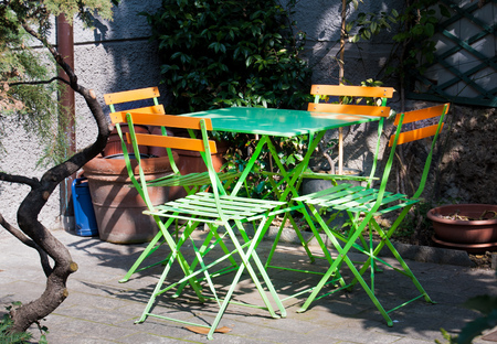 Green and orange chairs around a green table in essential style