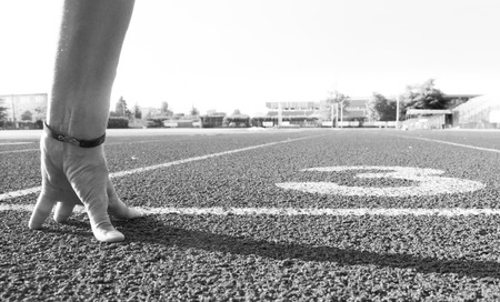 One hand of woman ready to run on the athletics track Фото со стока