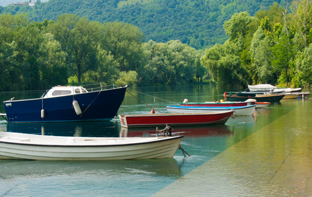 Colored boats anchored at the bank of the river and panorama on a large wood Imagens - 113305201