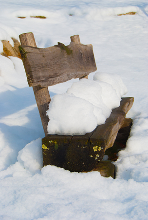Old wooden seat in the middle a the snow