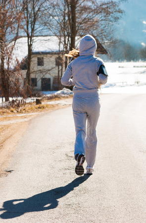 Girl running with gray tracksuit on a road with snow Standard-Bild