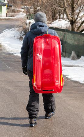 Guy gardant le bobsleigh sur l'épaule et s'éloignant dans une rue asphaltée