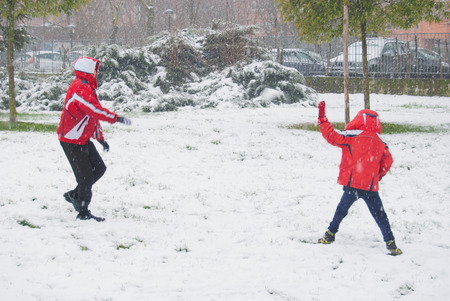 Children doing a snowball fight in a park during a snowfall Banco de Imagens