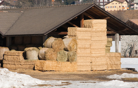 Bales of hay arranged under a roof of a barn