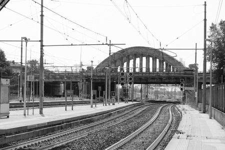 Train tracks of a small station with traffic light and concrete bridge