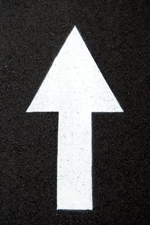 Vertical white arrow drawn on black asphalt Stok Fotoğraf