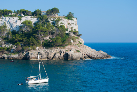 A white sailboat with a characteristic stretch of high and majestic coast of the Spanish island Stockfoto