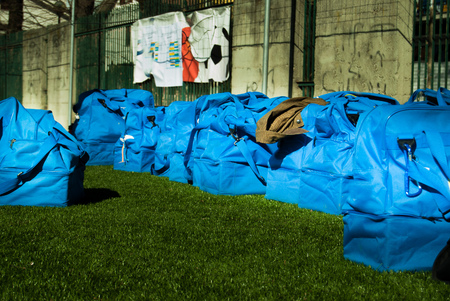 A group of light blue sport bags on the green grass of a football field Stock Photo