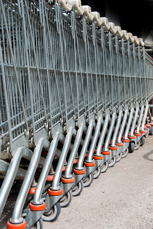 Queue of metal shopping carts left outside of the supermarket Stock Photo