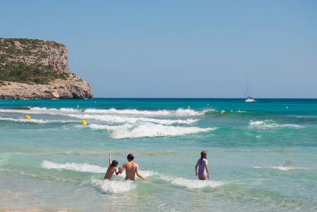 Waves of the Mediterranean seen from one of the beach of Menorca island with promontory and horizon line during a sunny day in the summer