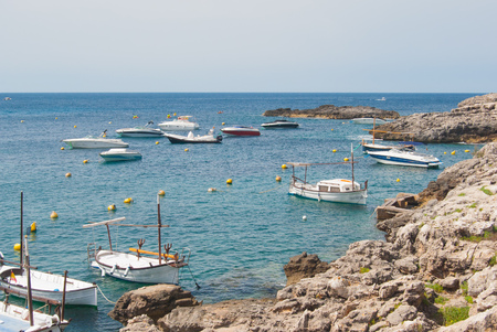 Boats and motorboats moored in a rocky inlet of the Mediterranean sea