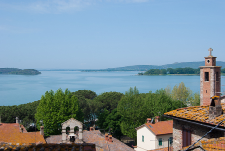 Panorama on roofs and Trasimeno lake in Umbria with little islands in the middle