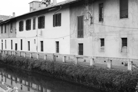 Old houses and their reflection on the Martesana river in northern Italy in black and white 스톡 콘텐츠
