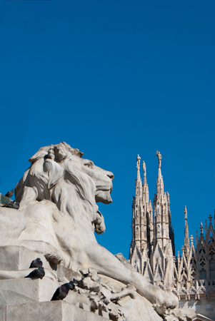 Statue of a had of a lion head dedicated to Victor Emmanuel II with pinnacles as a background