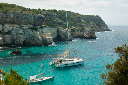 Catamaran and sailing boat in the turquoise sea of the spanish island with high cliff as panorama