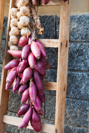 Braid of red onions and white garlic hanging outside on a wooden ladder