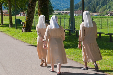 Groups of sisters in beige robes that walk and chat among themselves