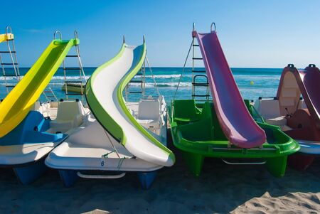 Pedalo with slides on the sandy shoreline of the sea during a sunny day