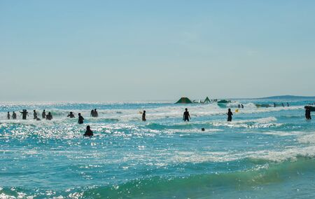 Black silhouettes of people enjoying the rough and blue sea during a sunny day in the summer 스톡 콘텐츠