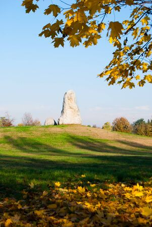 Two rocks on the top of a small hill with yellow leaves on the grass and others still on the maple tree that frame