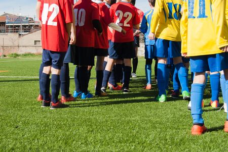 Young soccer players on a synthetic green field ready to line up to start the game
