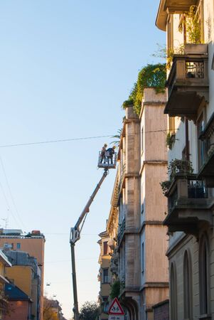 Two men with yellow helmets repair the fa?ade of a historic building of Milan 스톡 콘텐츠